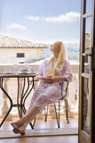Woman in pajamas sitting on balcony and holding book with eyes closed Royalty Free Stock Image