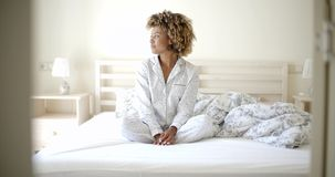 Woman In Pajamas Sitting On Bed stock footage