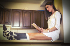 Woman in pajamas sitting at the counter in kitchen and using tablet Royalty Free Stock Image