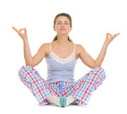 Woman in pajamas sitting on floor and meditating Stock Photography