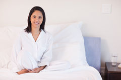 Woman in pajamas sitting on her bed Royalty Free Stock Photography
