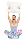 Woman in pajamas sitting and holding pillow Royalty Free Stock Images