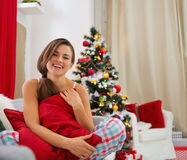 Woman in pajamas sitting near Christmas tree Stock Photo