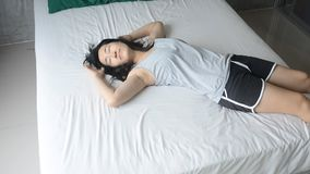 Woman with pajamas slowly laying down on bed stock video