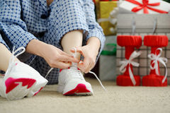 Woman in pajamas ties the laces of athletic shoes. Royalty Free Stock Photography