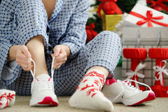 Woman in pajamas ties the laces of athletic shoes. Stock Photo