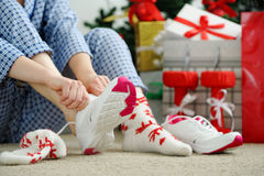 Woman in pajamas ties the laces of athletic shoes. Stock Image
