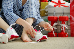 Woman in pajamas ties the laces of athletic shoes. Royalty Free Stock Photos