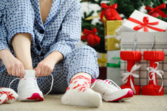 Woman in pajamas ties the laces of athletic shoes. Royalty Free Stock Image