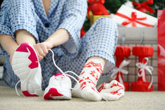 Woman in pajamas ties the laces of athletic shoes. Royalty Free Stock Images