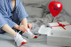 Woman in pajamas ties the laces of athletic shoes. Valentine`s D Royalty Free Stock Images