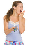 Woman in pajamas with TV remote control yawing Royalty Free Stock Image