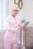Woman in pajamas using tablet at home Stock Photo