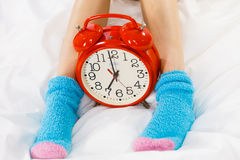 Woman in pajamas wearing furry warm socks Stock Images