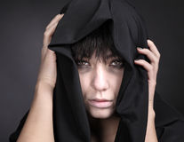 Woman with a pale face in black. Covered with black cloth. Scary woman. Studio shot on black background stock images