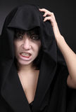 Woman with a pale face in black. Covered with black cloth. Scary angry woman. Studio shot on black background royalty free stock photography
