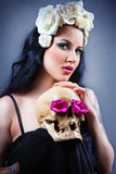 Woman with a pale face and skull. Skull stock photo