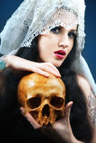 Woman with a pale face and skull. Skull royalty free stock image