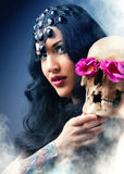 Woman with a pale face and skull. Skull royalty free stock photos