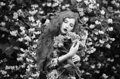 Art black and white photography. Unusual appearance. Woman with pale skin and long hair in peony dress on background of a flower garden. Black and white art Stock Photo