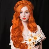 Woman with pale skin and long red hair. A woman with pale skin and long red hair in a light vintage dress and a pearl necklace. Girl with red lips and flowers in Royalty Free Stock Photos
