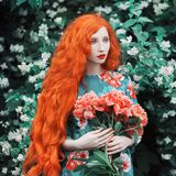 Woman with pale skin and long red hair in peony dress on background of a flower garden. Beautiful girl with red lips with a bouquet of peonies in hands. Beauty Stock Photo