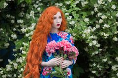 Woman with pale skin and long red hair in peony dress on background of a flower garden. Beautiful girl with red lips with a bouquet of peonies in hands. Beauty Royalty Free Stock Images