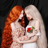 Woman with pale skin and very long white hair in a white dress. Two lesbian girlfriends. Fairy doll. Young beautiful unusual red-haired girl with curly hair and stock images