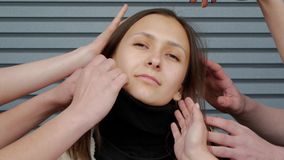 Woman among the palms of hands. Portrait of afraid young brown-haired woman who is touched by plenty of hands against the background of a striped wall. Alarmed stock video footage
