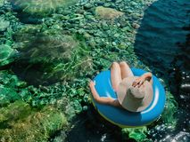 Woman with pamela on a float on a mountain river. Holidays in the mountain stock photos