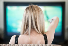 Woman with  panel switches  program on  TV Royalty Free Stock Image