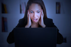 Woman in Panic Looking At A Computer Monitor. Businesswoman in panic looking at a computer screen in a dark room Stock Photos