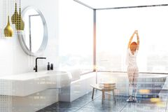 Woman in panoramic bathroom corner. Woman in corner of modern bathroom with tiled floor, white walls, panoramic windows, white bathtub and white sink with round stock photo