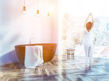 Woman in panoramic bathroom interior. Woman in pajamas standing in white bathroom corner with a black bathtub and a panoramic window with a tropical view. Toned royalty free stock images