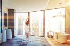 Woman in panoramic bathroom interior. Rear view of young woman standing in panoramic bathroom with cityscape. Comfortable bathtub and double sink with mirrors stock photography