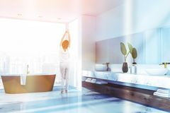 Woman in panoramic bathroom. Woman in pajamas stretching in panoramic bathroom interior with white marble floor, black tub and double sink. Toned image royalty free stock image