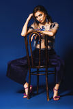 Woman in pants and floral silver top sitting on wooden chair Royalty Free Stock Image