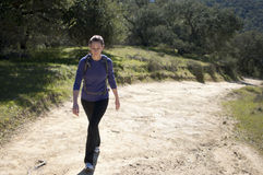 Woman in pants hikes up dirt fireroad, empty space right. On a sunny day Royalty Free Stock Photos