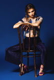 Woman in pants and top with blue flowers sitting on wooden chair Stock Photos