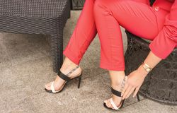 A woman in a pantsuit the color of live coral sits in a chair and straightens the clasp on sandals. stock images