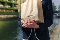 Woman with paper bag by canal Royalty Free Stock Image