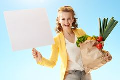 Woman with paper bag with groceries showing blank poster a Royalty Free Stock Photos