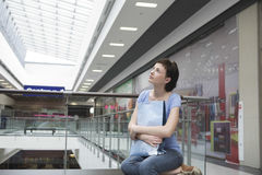 Woman With Paper Bag Looking Up In Shopping Centre Royalty Free Stock Photography