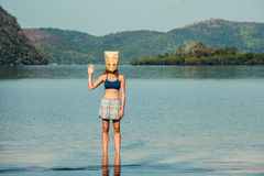 Woman with paper bag over head on tropical beach Royalty Free Stock Photos