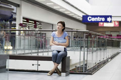 Woman With Paper Bag Sitting In Shopping Centre Stock Photography