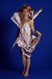 Woman in a paper dress. On a blue background royalty free stock images