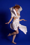 Woman in a paper dress. On a blue backgroundn stock photography