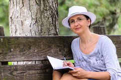 Woman with paper notebook in park Stock Image