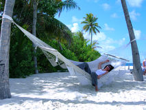 Woman in paradise. Woman on a beach in a hammock Royalty Free Stock Photo