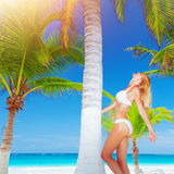 Woman on paradise beach. Attractive sexy woman relaxing on paradise beach, cute blond model with perfect body standing near palm tree, luxury tropical resort Royalty Free Stock Images